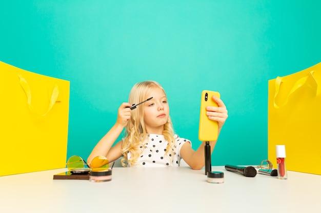 Счастливая маленькая девочка перед камерой телефона, делая видео для видеоблога. работаю блоггером, записываю видеоурок для интернета.