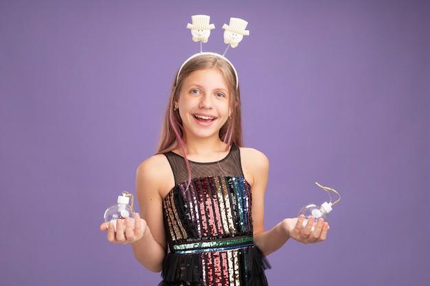 반짝이 파티 드레스와 보라색 배경 위에 유쾌하게 서있는 카메라를보고 크리스마스 공을 들고 재미있는 머리띠에 행복 한 어린 소녀