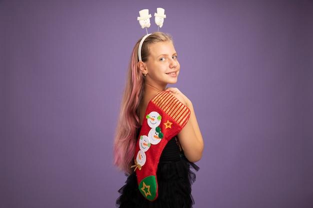 Счастливая маленькая девочка в блестящем вечернем платье и забавной повязке на голову, держащая рождественский чулок, глядя в камеру, весело улыбаясь, стоя на фиолетовом фоне