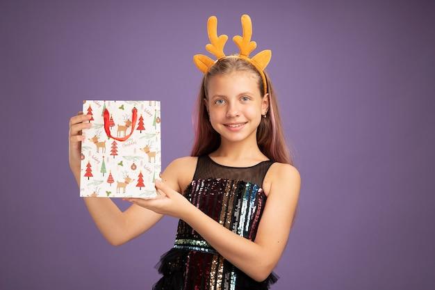 キラキラパーティードレスと紫色の背景の上に元気に立って笑顔のカメラを見て贈り物とクリスマスの紙袋を保持している鹿の角を持つ面白いヘッドバンドの幸せな少女