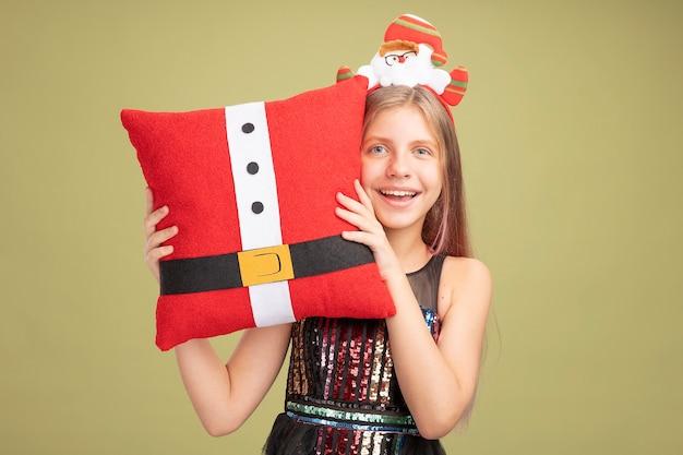 반짝이 파티 드레스와 산타가 녹색 배경 위에 유쾌하게 서있는 카메라를보고 재미있는 베개를 들고 행복 한 어린 소녀