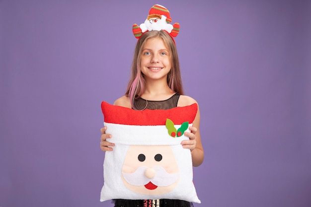 紫色の背景の上に立っている顔に笑顔でカメラを見て面白い枕を保持しているサンタとキラキラパーティードレスとヘッドバンドの幸せな少女
