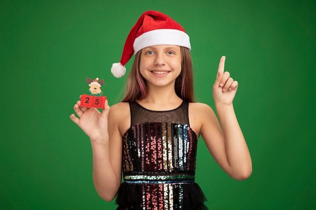 キラキラパーティードレスとサンタ帽子の幸せな少女は、緑の背景の上に元気に立って笑顔の人差し指を示す日付25のおもちゃの立方体を示しています