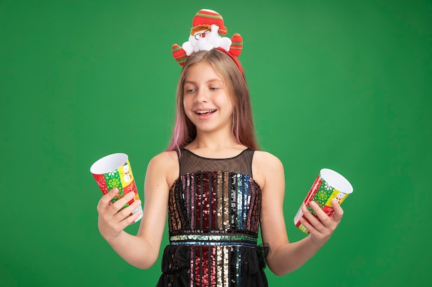 반짝이 파티 드레스와 산타 머리띠에 행복 한 어린 소녀 녹색 배경 위에 유쾌 하 게 서 웃 고 두 개의 다채로운 종이 컵을 들고