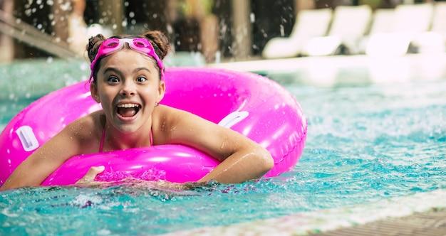 暑い夏の日にプールでピンクのインフレータブルリングで遊んでゴーグルの幸せな少女。子供たちは泳ぐことを学びます。子供の水のおもちゃ。家族のビーチでの休暇。