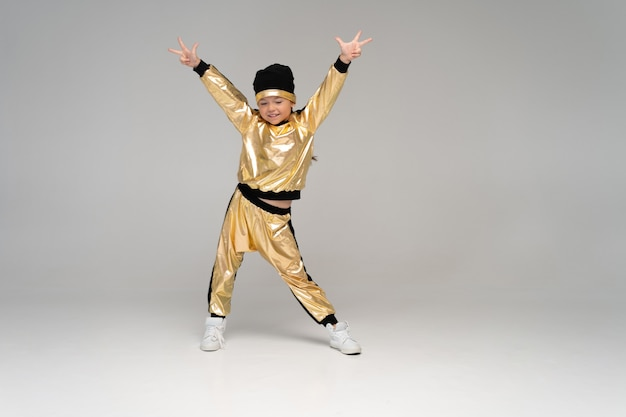 白い表面で隔離の金のスーツのダンスで幸せな少女
