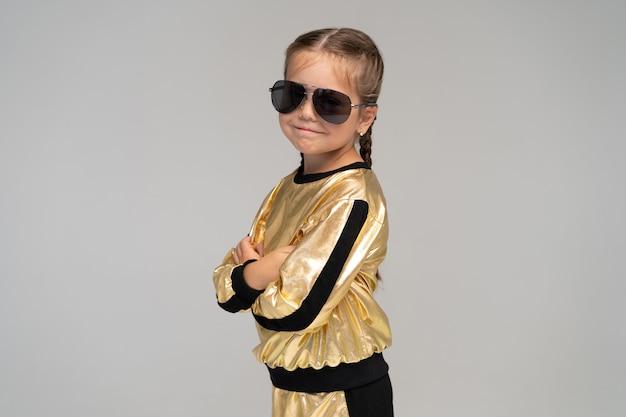 Счастливая маленькая девочка в золотом костюме танцует изолированно на белой поверхности