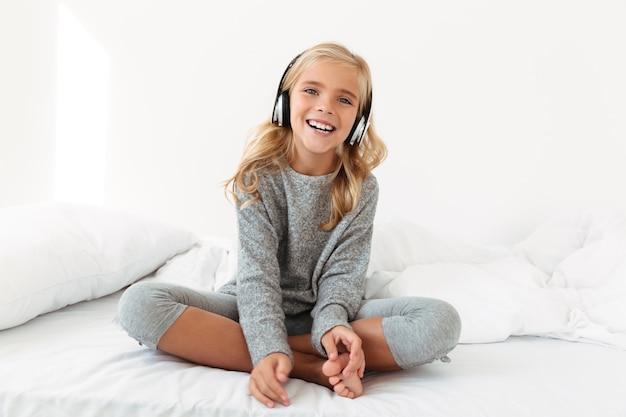 彼女のベッドに座って音楽を聴く灰色のパジャマでの幸せな女の子