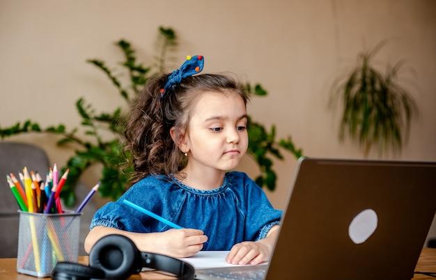 Счастливая маленькая девочка в наушниках улыбается и делает заметки в блокноте, общаясь с учителем через видео