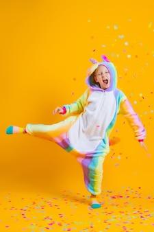 Счастливый маленькая девочка в кигуруми, танцы единорога на желтой стене среди разноцветных конфетти