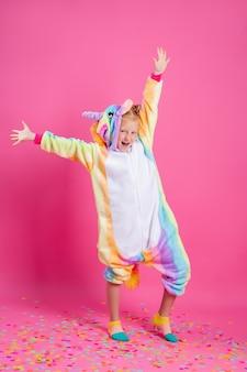 Счастливая маленькая девочка в единороге кигуруми на розовой стене радуется разноцветному конфетти