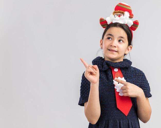Счастливая маленькая девочка в вязаном платье в красном галстуке с забавным рождественским ободком на голове смотрит в сторону, указывая указательным пальцем на копировальное пространство