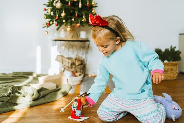 パジャマ姿の幸せな少女がクリスマスのおもちゃで遊んでいる鹿鹿子供はクリスマスの飾りで飾られた部屋で遊んでいます。メリークリスマスと新年あけましておめでとうございますのコンセプト。家族の居心地の良い瞬間