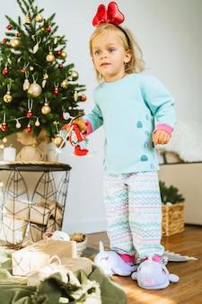 パジャマ姿の幸せな少女がクリスマスのおもちゃで遊んでいる鹿鹿子供はクリスマスの装飾で飾られた部屋で遊んでいますメリークリスマスと幸せな新年のコンセプト。家族の居心地の良い瞬間