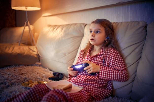 Счастливая маленькая девочка в пижаме, сидя на диване, ест пиццу