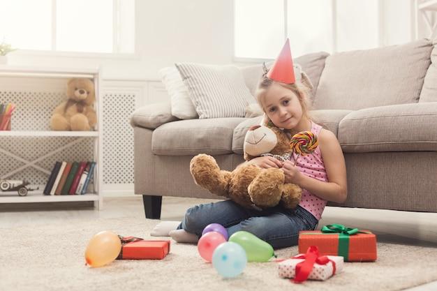 誕生日を祝うパーティーハットの幸せな少女。テディベアを抱きしめて、贈り物や風船の中で床に座っている笑顔の子供。休日のコンセプト、コピースペース