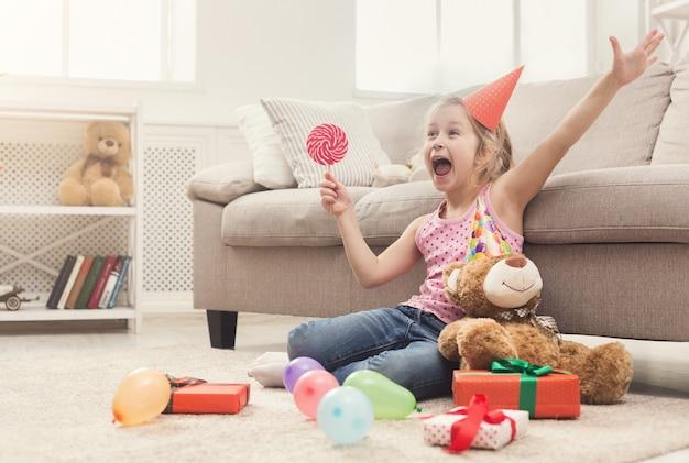 誕生日を祝うパーティーハットの幸せな少女。贈り物や風船の中で床に座って、ロリポップを持って笑顔の子供。休日のコンセプト、コピースペース