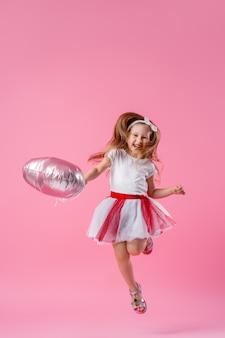 Счастливая маленькая девочка в пышной юбке и банте на голове для прыжков на день рождения