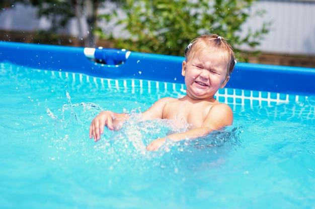 Счастливая маленькая девочка в красном купальнике скача в открытый бассейн дома. девочка учится плавать. водные развлечения для детей.