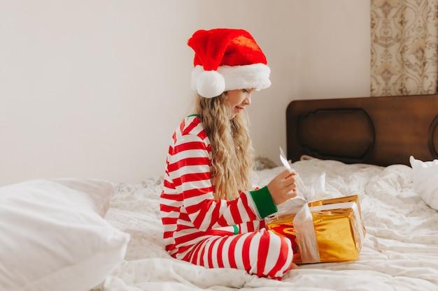 Счастливая маленькая девочка в шляпе санта-клауса сидит на кровати с рождественским подарком. рождественский малыш, ребенок.