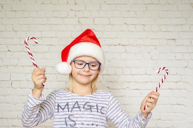 白いレンガの壁の背景にキャンディケインのお菓子を保持しているサンタの帽子と眼鏡の幸せな少女