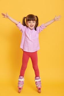 Счастливая маленькая девочка в рубашке и леггинсах с роликовыми коньками позирует в помещении с поднятыми руками