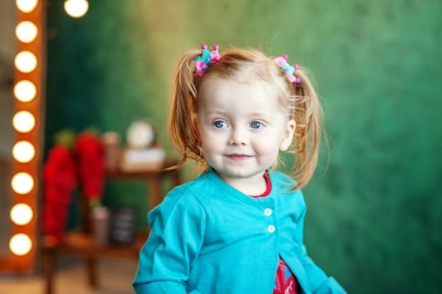 Счастливый маленькая девочка в шортах, сидя на стуле.