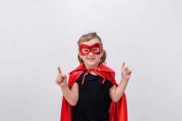Счастливая маленькая девочка в костюме супергероя, показывая руки вверх
