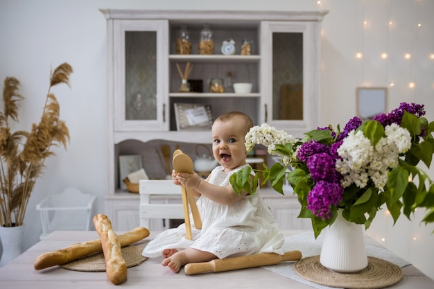 Счастливая маленькая девочка в белом платье играет с деревянными шпателями на кухонном столе
