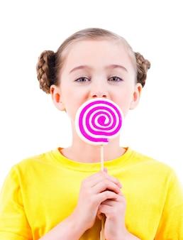 色付きのキャンディーを食べる黄色のtシャツの幸せな少女-白で隔離。