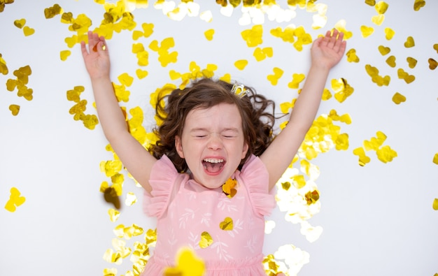 Happy little girl is lying with golden confetti on a white background with a place for text. happy childhood