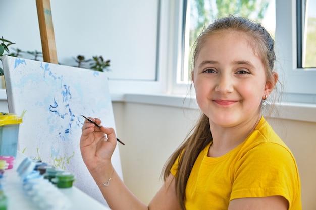행복한 어린 소녀가 구아슈로 그림을 그리고 있습니다. 집에서 그림을 그리는 행복한 어린 소녀. 소녀는 숫자로 그림을 그립니다. 클로즈업, 선택적 초점.