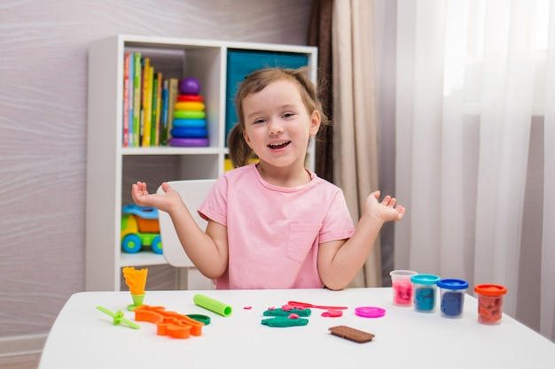 A happy little girl is playing play-doh at a table in the children's room