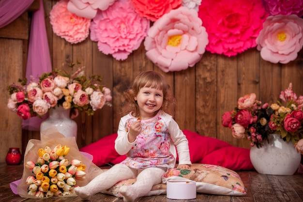 Happy little girl is sitting on pillows on wooden floor, surrounded by flowers .