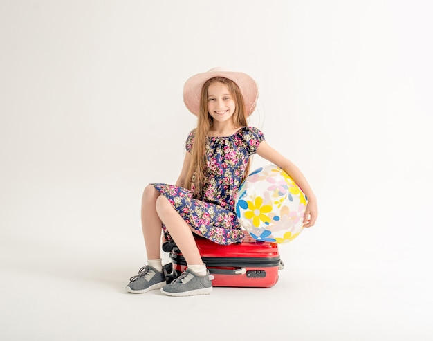 Happy little girl is sitting on a suitcase with a ball