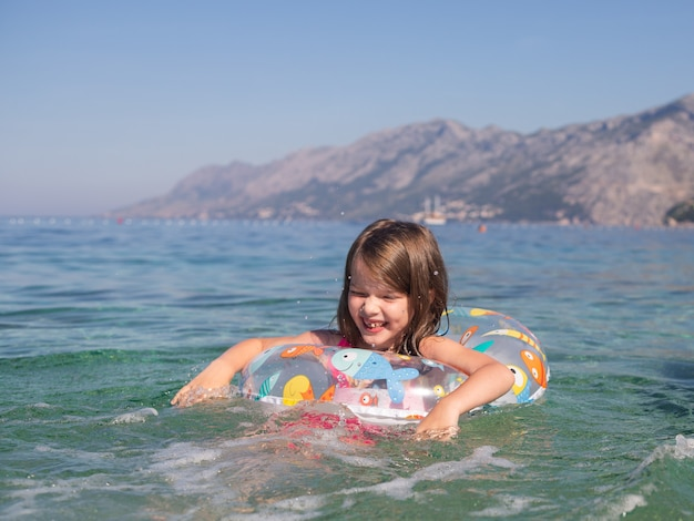 Happy little girl is swimming in an inflatable circle in the sea, adriatic sea, croatia