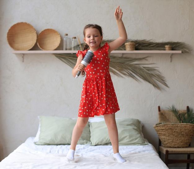 Счастливая маленькая девочка прыгает на кровати, держа щетку для волос, как микрофон, открытый рот, пение имитирует, воображает себя настоящей певицей