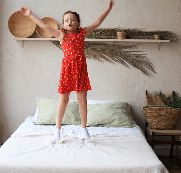 Счастливая маленькая девочка прыгает на кровати, поет песню.