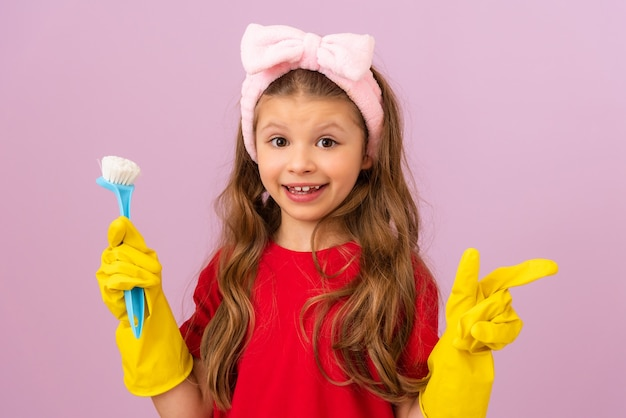 A happy little girl keeps the house clean. rubber gloves and a scrub brush.