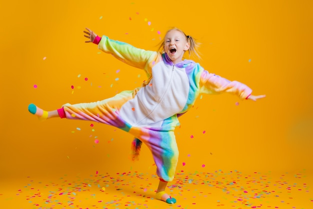 Happy little girl in kigurumi unicorn dancing on a yellow wall among multicolored confetti