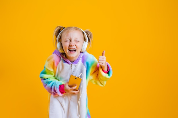A happy little girl in a kigurumi unicorn listens to music in headphones holding a smartphone