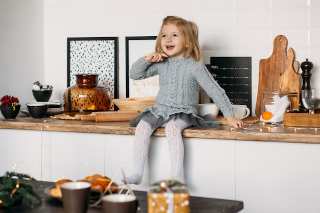 Happy little girl in kitchen at home.