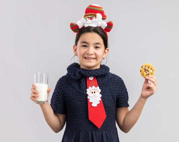 Happy little girl in knit dress wearing red tie with funny christmas rim on head holding glass of milk and cookie smiling cheerfully