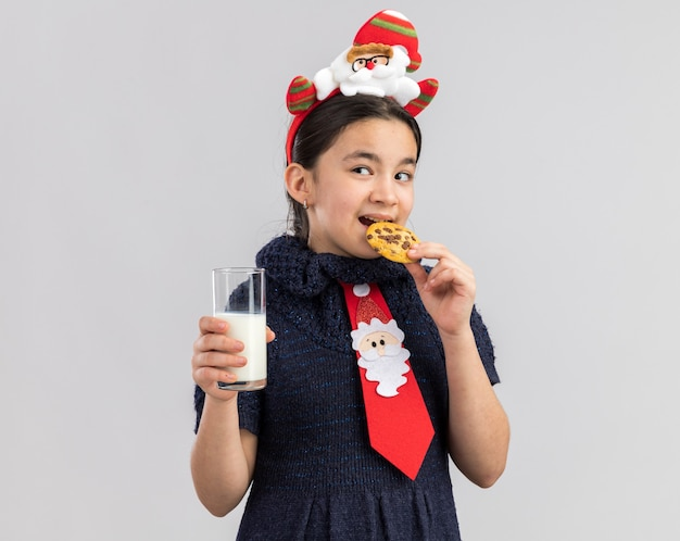 Happy little girl in knit dress wearing red tie with funny christmas rim on head holding glass of milk eating cookie