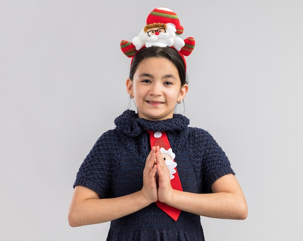 Bambina felice in abito in maglia che indossa cravatta rossa con bordo divertente di natale sulla testa che tengono le mani insieme come gesto di namaste