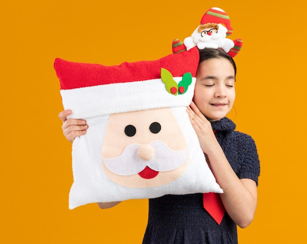 Happy little girl in knit dress wearing red tie with funny rim on head holding christmas pillow with closed eyes smiling