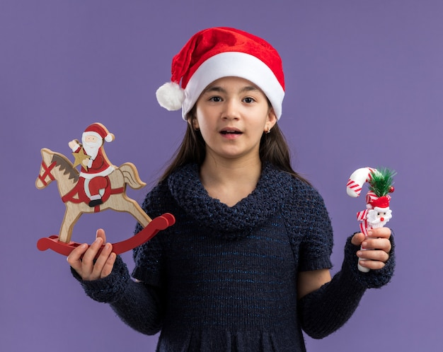 Happy little girl in knit dress wearing santa hat holding christmas toys looking at camera smiling cheerfully standing over purple background