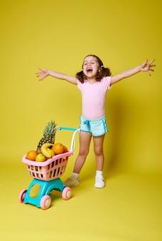 행복 한 어린 소녀, 팔 웃 고 열리고 맛있는 이국적인 과일 가득한 그녀의 쇼핑 트롤리 근처 노란색에 서 서.