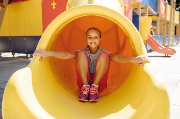 Happy little girl leisures on playground, childhood. child climbing on suspension bridge