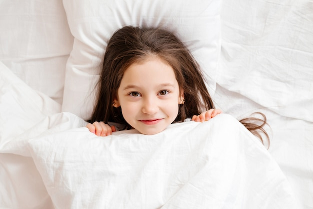 Happy little girl lies in bed at home in the morning. healthy baby sleep. white bed linen, space for text